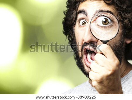 portrait of young scientific looking through a magnifying glass against a nature background