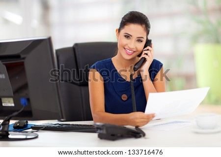 portrait of young secretary answering telephone - stock photo
