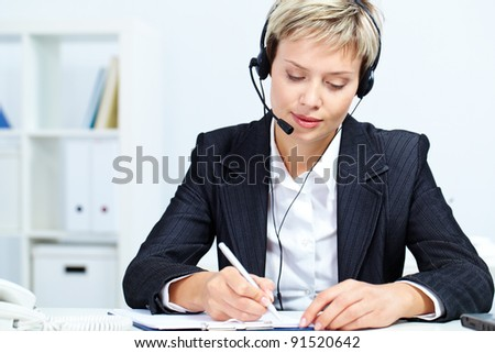 Portrait of young secretary with headset sitting at table and making notes