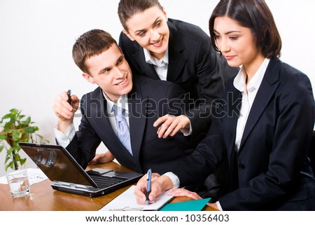 Portrait of young secretary writing something in her notebook while two businesspeople sitting near by looking at her