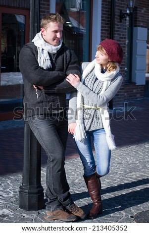 Portrait of young sensual couple in cold winter weather. Love and kiss. Young people. Snow lovers kiss city. Fashion clothing.Young people walking around the city in the winter