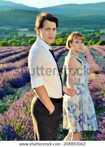 Portrait of young sensual loving couple in a lavender field at sunset backlight. Provence, France. Cross processing from RAW file - stock photo