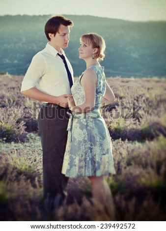 Portrait of young sensual loving couple in a lavender field at sunset backlight. Provence, France. Filtered image, cross processing from RAW file and vintage affect applied - stock photo