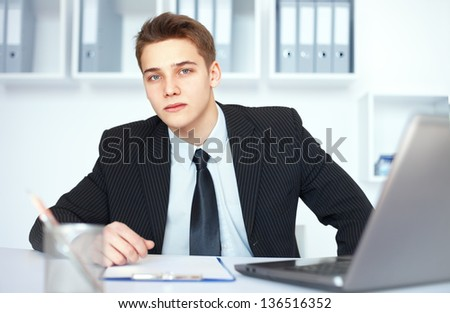 Portrait of young serious businessman at his workplace in bright office
