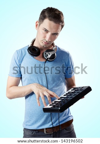 Portrait of young serious deejay with headphones pressing keys on midi controller.Gradient blue background. - stock photo