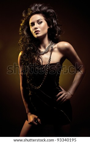 Portrait of young sexy beautiful woman with long black hair on dark background - stock photo