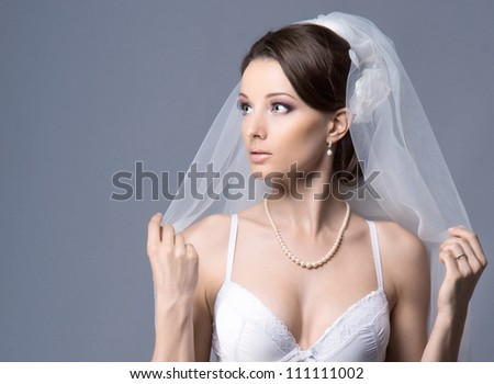 Portrait of young sexy bride over blue - stock photo