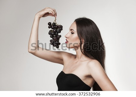 Portrait of young sexy brunette eating  grapes. Beautiful woman dressed in black posing in studio.  - stock photo