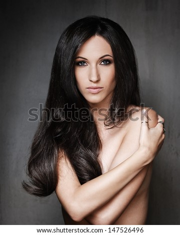 Portrait of young sexy brunette holding hands around her - stock photo