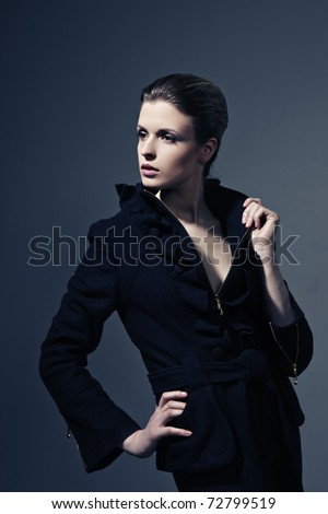 Portrait of young sexy glamorous woman on black background promoting clothes - stock photo