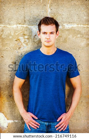 Portrait of Young Sexy Man.  Wearing a blue T shirt, jeans, a young handsome guy is standing against a old concrete wall, confidently looking at you. - stock photo