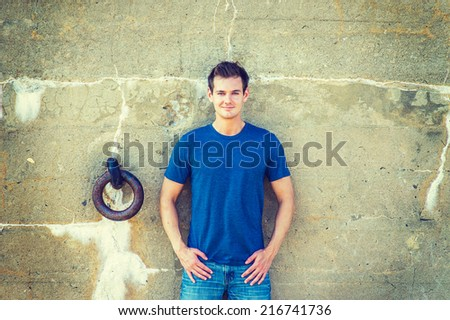 Portrait of Young Sexy Man.  Wearing a blue T shirt, jeans, a young handsome guy standing against an old concrete wall with a rusty metal ring, looking at you. Concept of timing, history and life.