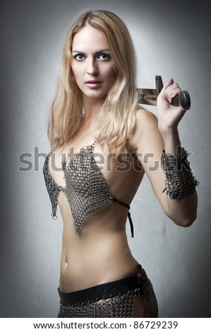 Portrait of young sexy model. Woman warrior with sword in seductive armour looking at camera. Joan of Arc - stock photo