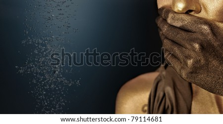 Portrait of young sexy woman in golden paint against dark background. Fuel crisis concept