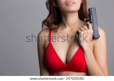 Portrait of young sexy woman in red bra holding a gun - stock photo