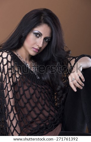 portrait of young sexy young indian woman posing on brown background - stock photo
