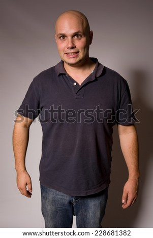 Portrait of young silly man on a dark background - stock photo