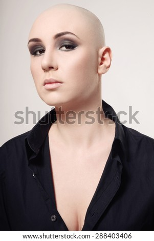 Portrait of young skinhead woman with smoky eyes make-up - stock photo