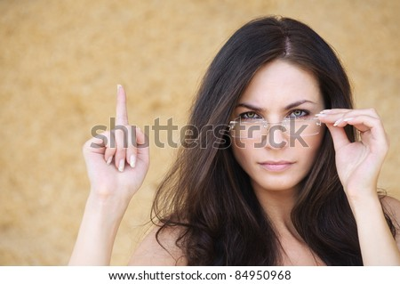 Portrait of young smart brunette woman wearing eyeglasses against yellow background. - stock photo