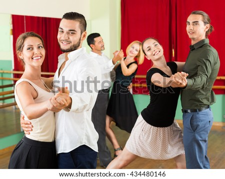 Portrait of young smiling adults having grave dances  in class - stock photo