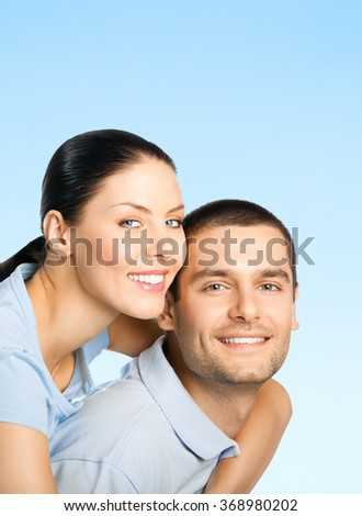 Portrait of young smiling amorous attractive couple, over blue sky background, with blank copyspace area for text or slogan