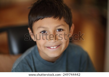 Portrait of young smiling boy with very shallow depth of field and warm tones - stock photo