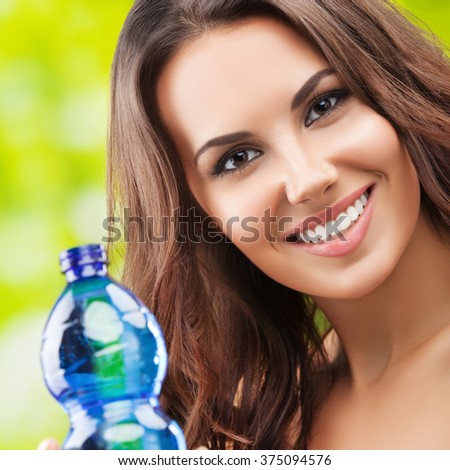 Portrait of young smiling brunette woman with bottle of water, outdoor. Healthy lifestyle, beauty and dieting concept. - stock photo