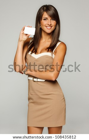 Portrait of young smiling business woman in beige dress holding empty credit card isolated on gray background - stock photo