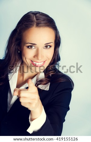 Portrait of young smiling business woman pointing finger at viewer