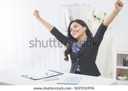 portrait of Young smiling business woman raise arm after finishing her work