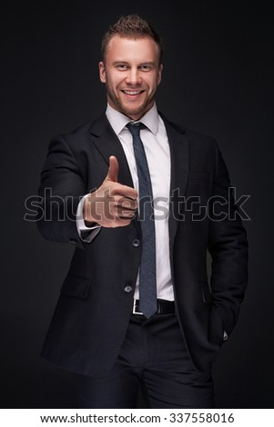 Portrait of young smiling businessman isolated on dark background - stock photo
