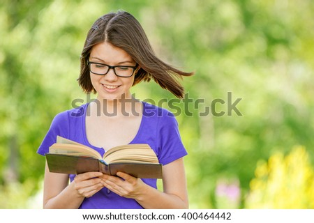 Portrait of young smiling cheerful woman wearing eyeglasses and violet blouse reading interesting book at summer green park.