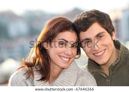 Portrait of young smiling couple in town - stock photo