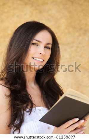 Portrait of young smiling dark-haired pretty woman holding a book against yellow backgroud. - stock photo