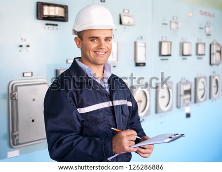 Portrait of young smiling engineer taking notes at control room - stock photo