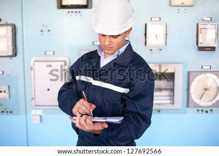 Portrait of young smiling engineer taking notes in control room - stock photo