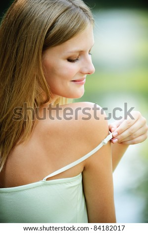 Portrait of young smiling fair-haired woman putting out strap of her dress at summer green park. - stock photo