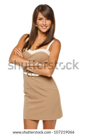 Portrait of young smiling female in beige dress standing with folded hands, over white background - stock photo
