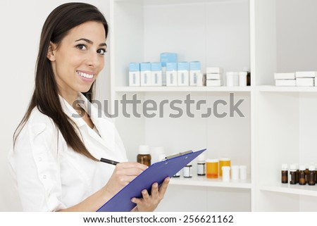 Portrait of young smiling female pharmacist standing near shelf with drugs   holding a clipboard and looking at camera. - stock photo