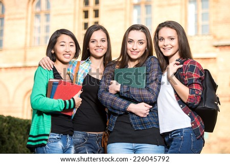 Portrait of young smiling female students. The university building in the background. - stock photo