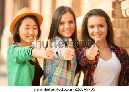 Portrait of young smiling female students with university building in the background. - stock photo