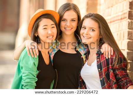 Portrait of young smiling female students with university building in the background.