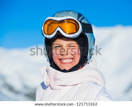 Portrait of young smiling girl a ski outfit at winter outdoor in the Zillertal Arena, Austria - stock photo