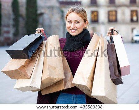 Portrait of young smiling girl with many paper bags from her shopping outdoors - stock photo