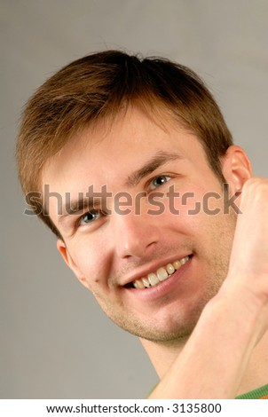 Portrait of  young smiling guy emotionally gesticulating hands, close up, vertical - stock photo