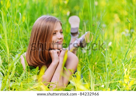 Portrait of young smiling happy blond woman lying in grass, propping up her face and looking somewhere at summer green park. - stock photo