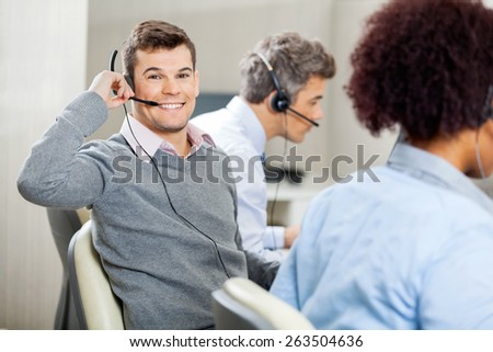 Portrait of young smiling male customer service representative using headset while colleagues working in office - stock photo