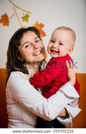 Portrait of young smiling mother with her happy baby - indoor - stock photo