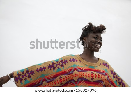 Portrait of young smiling woman holding her arms out in traditional clothing from Africa - stock photo