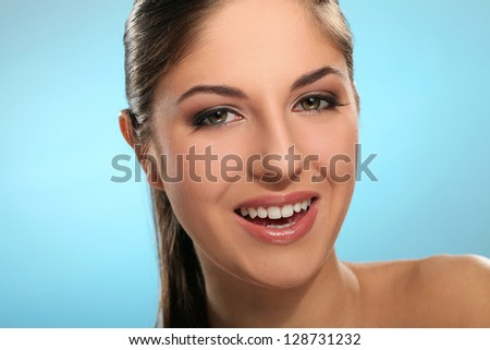 Portrait of young smiling woman isolated over blue background - stock photo